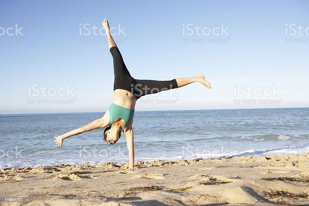 Young Woman In Fitness Clothing Turning Cartwheel On Beach stock photo