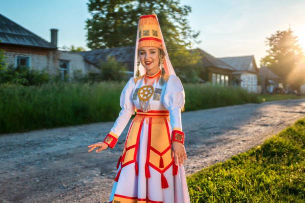 Young Woman in Folk Mari Dress at Sunset on Village Street Cute young woman dressed in women's traditional clothes and jewelry which are recreated according to medieval samples of the Mari people. The young woman stands on a lawn next to the country road. She is smiling looking at the camera. Shooting in a countryside on a summertime at a sunset, Republic of Mari El in Russia's Volga region eastern europe stock pictures, royalty-free photos & images