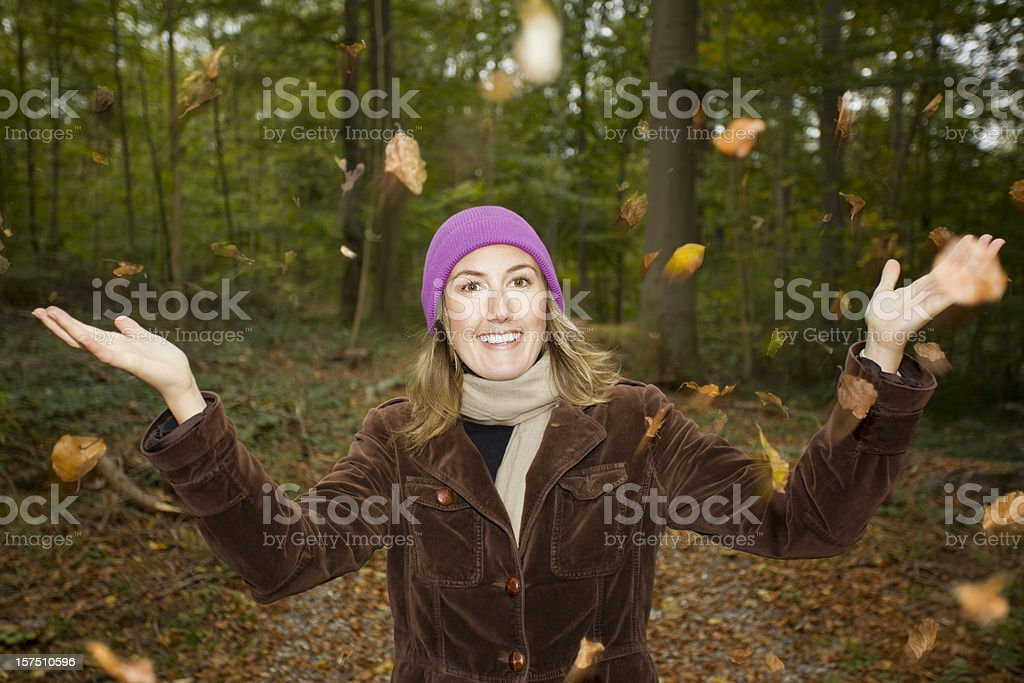 Young Woman in Forest with Autumn Leaves Blowing in Wind royalty-free stock photo