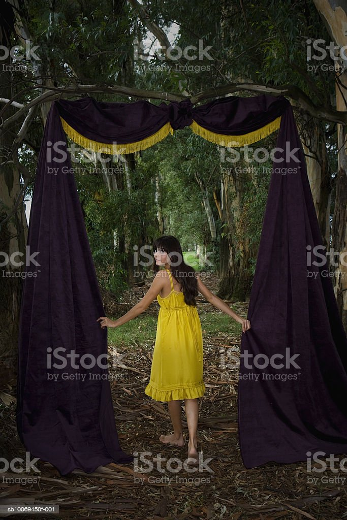 Young woman in forest with door made up of curtain royalty-free stock photo