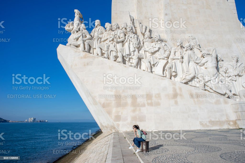 A young woman in front is watching the monument. A girl from Japan sits on a kilon. stock photo