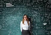 Businesswoman standing near blackboard with formulas and figures.