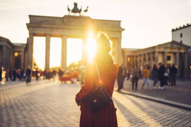 junge frau vor dem brandenburger tor in berlin, deutschland - deutsche frauen stock-fotos und bilder