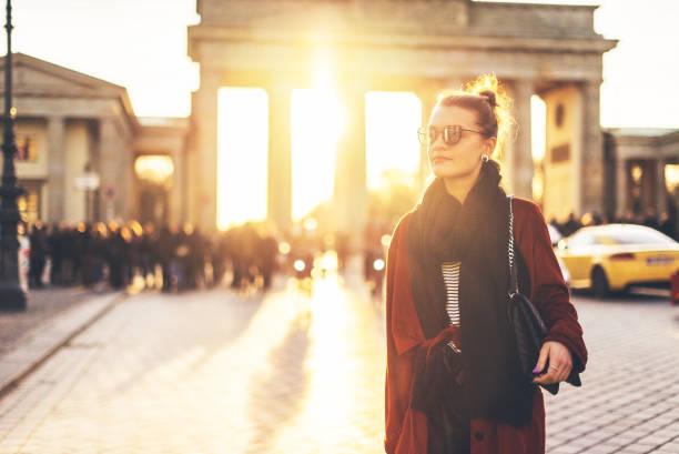 junge frau vor dem brandenburger tor in berlin, deutschland - berlin mitte stock-fotos und bilder