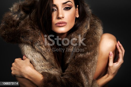 Close up portrait of young woman in fur coat posing in studio. She has her arms crossed and look at a camera