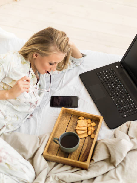 커피와 침대에 누워 노트북의 컵과 안경에 젊은 여자 - 커피 마실 것 뉴스 사진 이미지