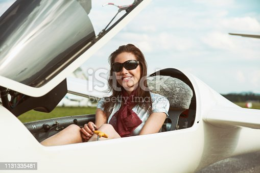Woman sitting in an open glider plane on a small airport. Happy and smiling.