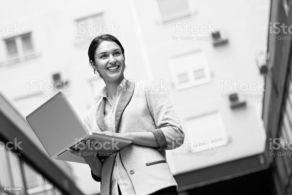 Young woman in gray business suit, holding laptop and smiling. - Photo