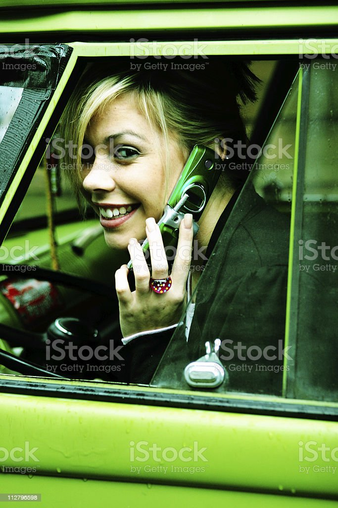 young woman in green car on cell phone royalty-free stock photo