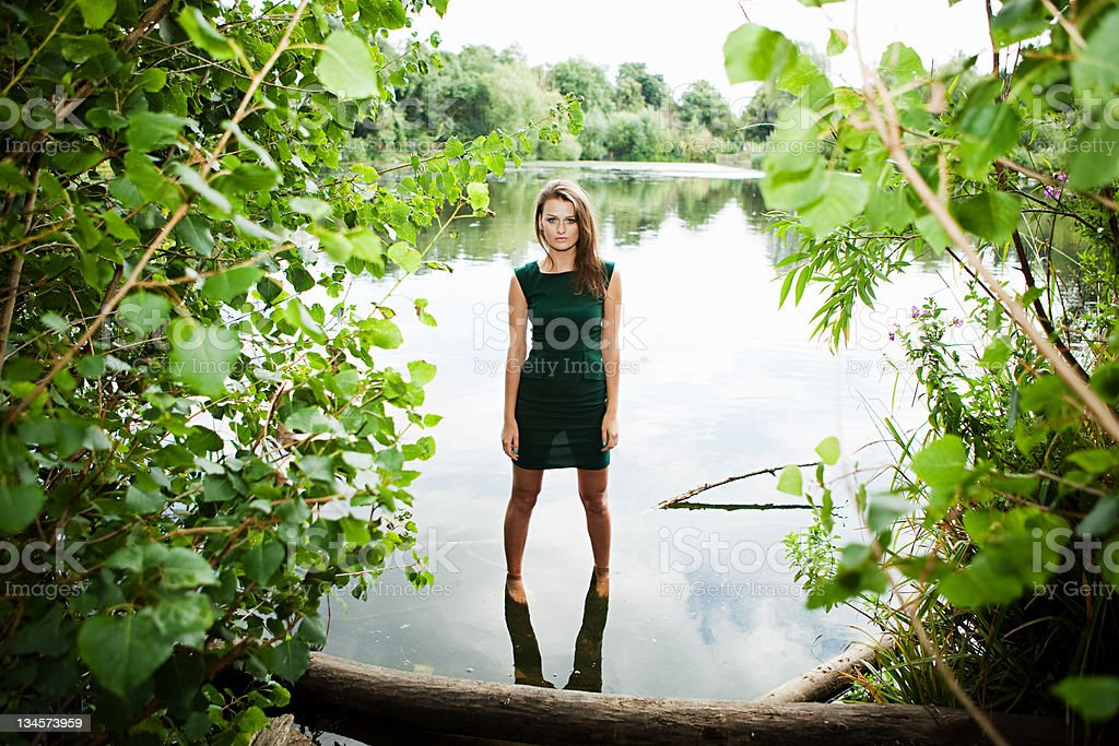 Young woman in green dress, standing in a lake stock photo