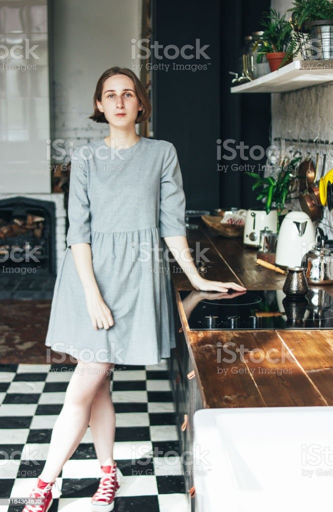 Young woman in grey dress on the kitchen, scandinavian interior, slow...