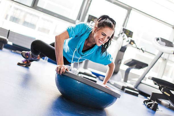 Young woman in gym - exercising with balance training equipment stock photo
