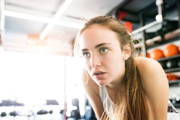 junge frau im fitness-studio, in weißen tank-top, ruhen, schwitzen im gesicht. - konzentrationsübungen stock-fotos und bilder