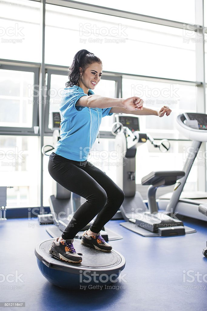Young woman in gym - standing on balance training equipment stock photo