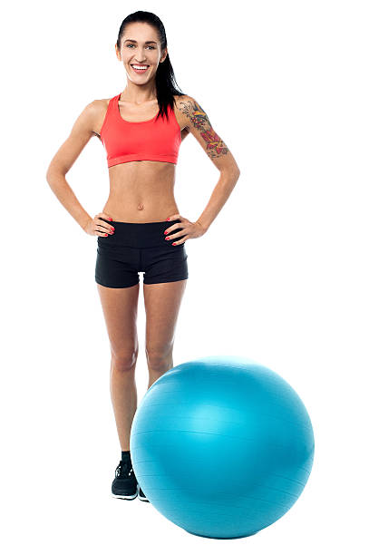 Young woman in gym wear with exercise ball stock photo