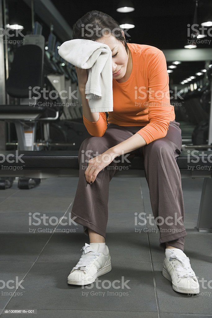 Young woman in gym wiping sweat royalty-free stock photo