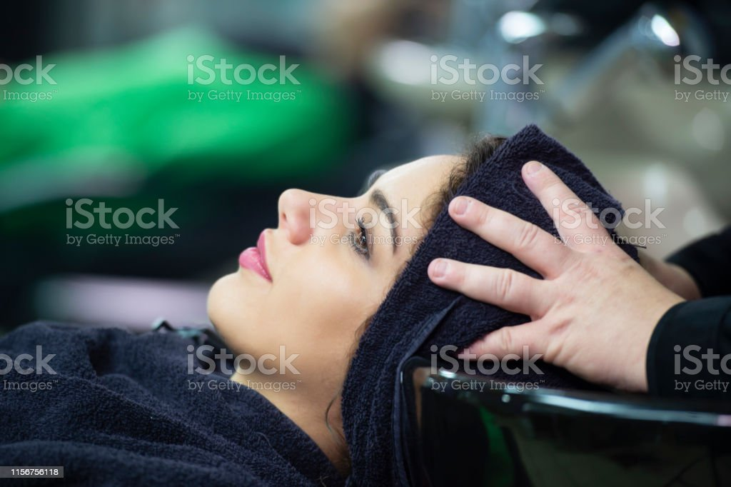 young woman in hairdresser salon cleaning hair