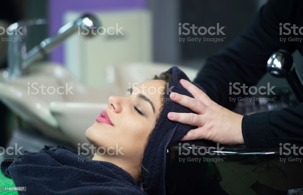 young woman in hairdresser salon, towel on head