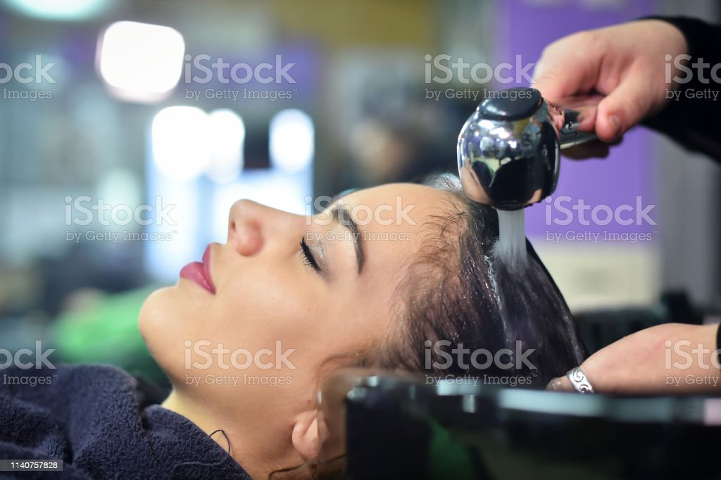 young woman in hairdresser salon washing hair