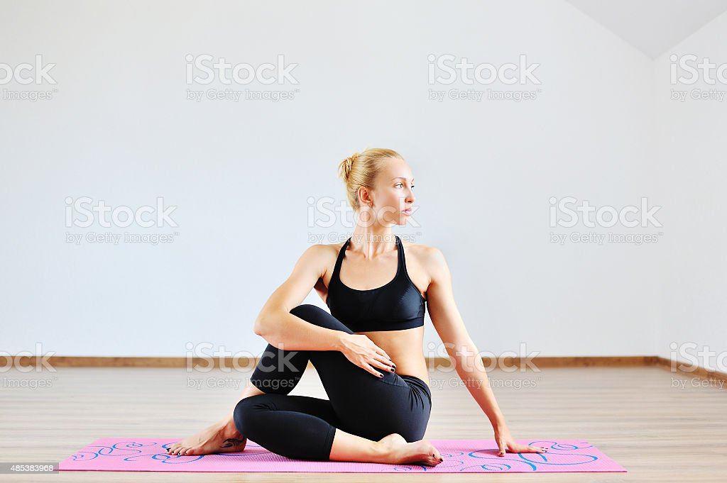 Young woman in half spinal twist pose on mat stock photo