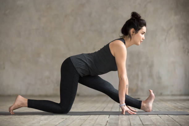 Young woman in Half splits pose Young sporty woman practicing yoga, doing Half splits exercise, Ardha Hanumanasana pose, working out, wearing sportswear, black pants and top, indoor full length, gray wall in yoga studio hanuman stock pictures, royalty-free photos & images