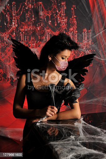 Young woman in halloween black fallen angel costume wearing protective medical face mask against coronavirus Covid-19. New normal and Halloween concept