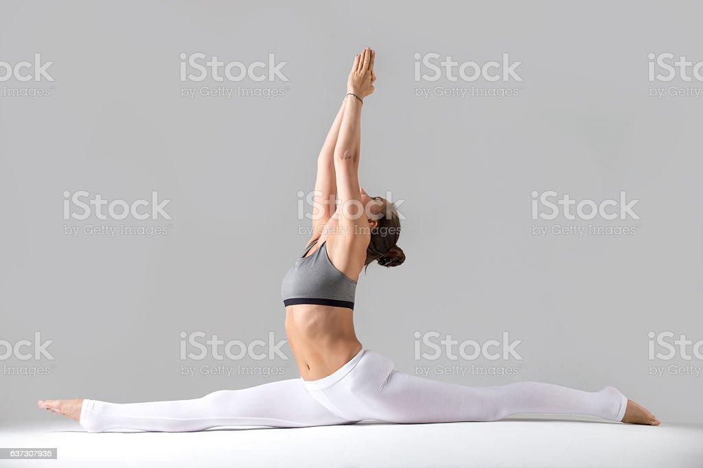 Young woman in Hanumanasana pose, grey studio background stock photo