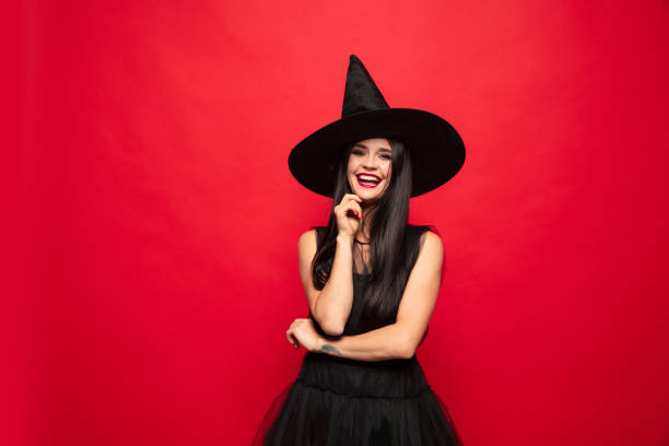 Young woman in hat and dress as a witch on red background stock photo