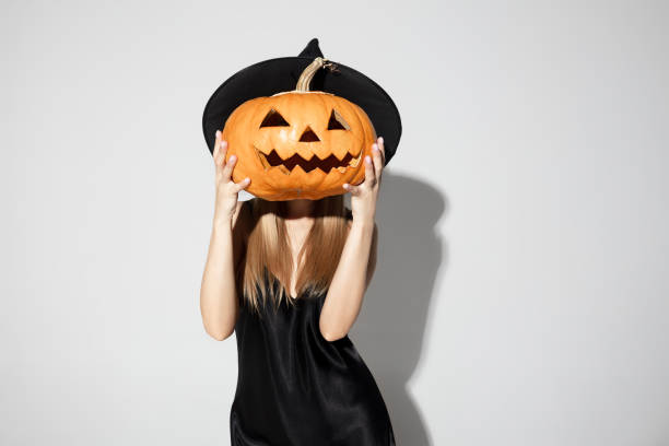 Young woman in hat as a witch on white background stock photo