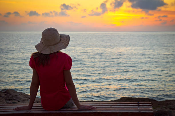 Young woman in hat sitting and looking at sunset stock photo