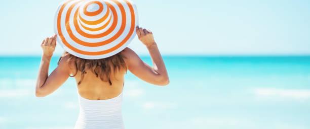 Junge Frau im Hut, die am Strand steht. Rückansicht – Foto