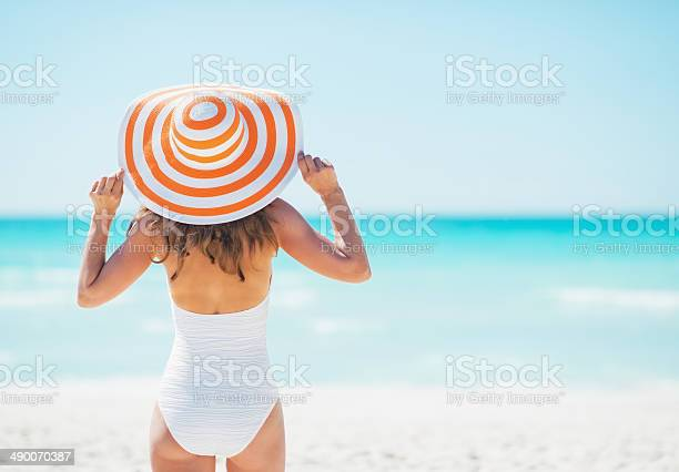 Young woman in hat standing on beach rear view picture id490070387?b=1&k=6&m=490070387&s=612x612&h=sr5si iqx5vghk64fht7tisplm ztjm lqzepe02rdu=