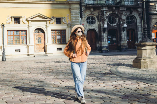 Young woman in hat walking in the old sunny city wearing a protective mask stock photo