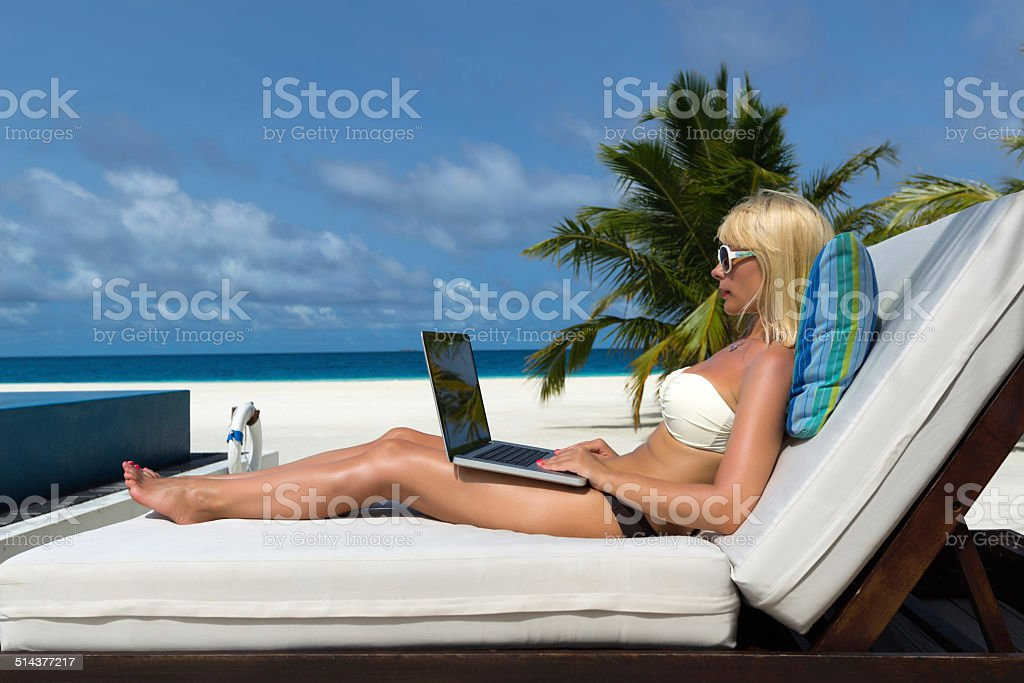 Young woman in hat with laptop at the beach stock photo