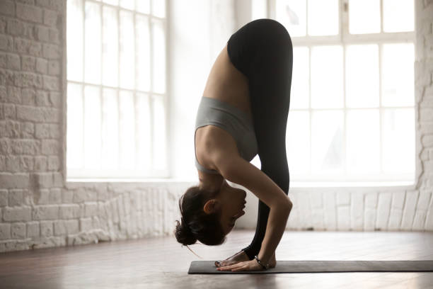 Young woman in head to knees exercise, white loft studio Young attractive sporty woman practicing yoga, standing forward bend exercise, head to knees, uttanasana pose, working out, wearing sportswear, white loft studio background, full length, side view namaskard geothermal area stock pictures, royalty-free photos & images