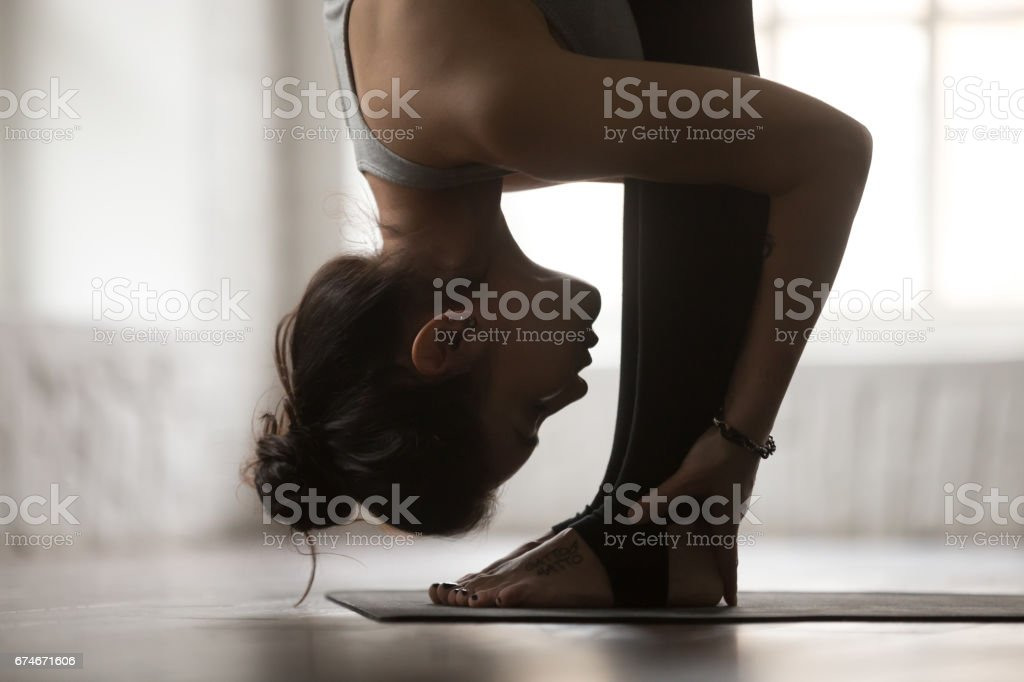 Young woman in head to knees exercise, white studio, closeup stock photo