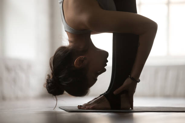 Young woman in head to knees exercise, white studio, closeup Young attractive sporty woman practicing yoga, standing forward bend exercise, head to knees, uttanasana pose, working out, wearing sportswear, white loft studio background, side view, close up namaskard geothermal area stock pictures, royalty-free photos & images