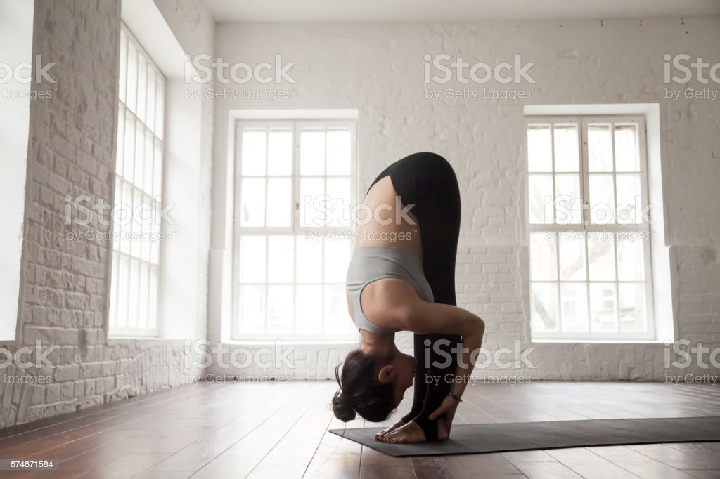 Young woman in head to knees pose, white loft studio stock photo