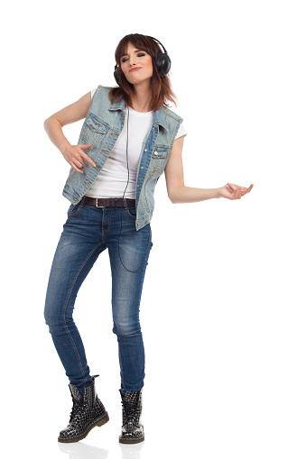 Young woman in jeans vest, black boots and headphones is listening to the music and playing air guitar. Full length studio shot isolated on white.