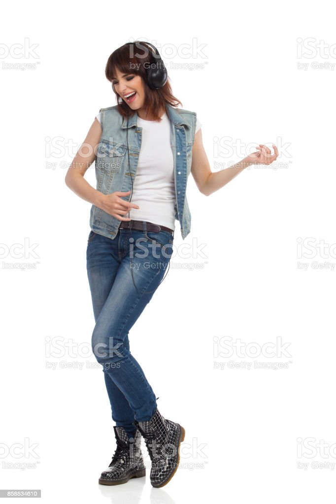 Young Woman In Headphones Is Singing And Playing Air Guitar stock photo