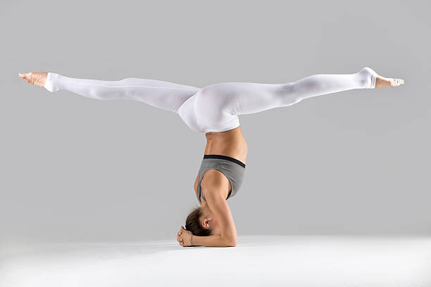 young woman in headstand exercise, grey studio background - spagat stock-fotos und bilder