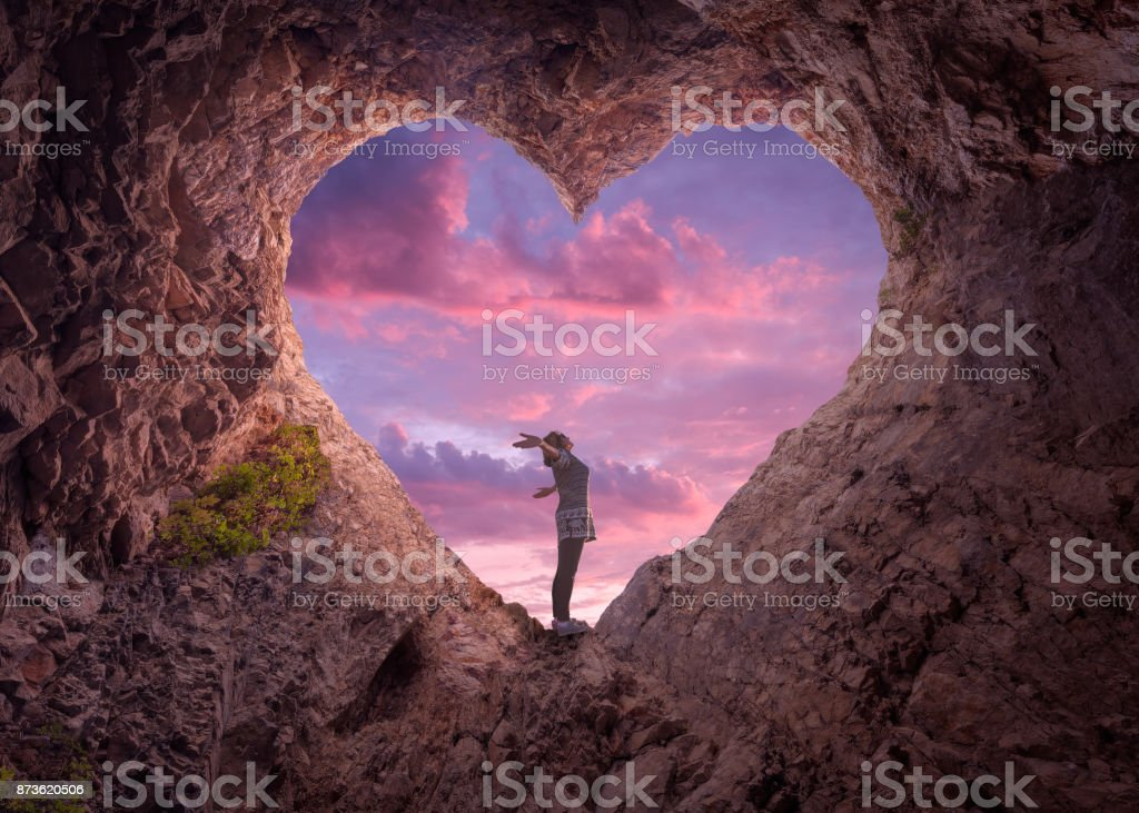 Young woman in heart shape cave towards the beautiful sky Happy woman enjoying in idyllic mountain nature, celebrating freedom and rising her arms while standing toward the setting sun. Valentines day concept. Adult Stock Photo