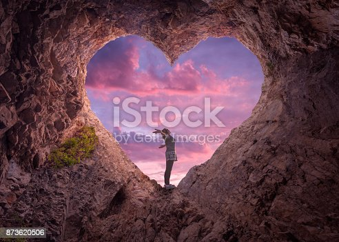 Happy woman enjoying in idyllic mountain nature, celebrating freedom and rising her arms while standing toward the setting sun. Valentines day concept.