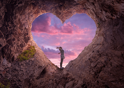 Young Woman In Heart Shape Cave Towards The Beautiful Sky Stock Photo - Download Image Now