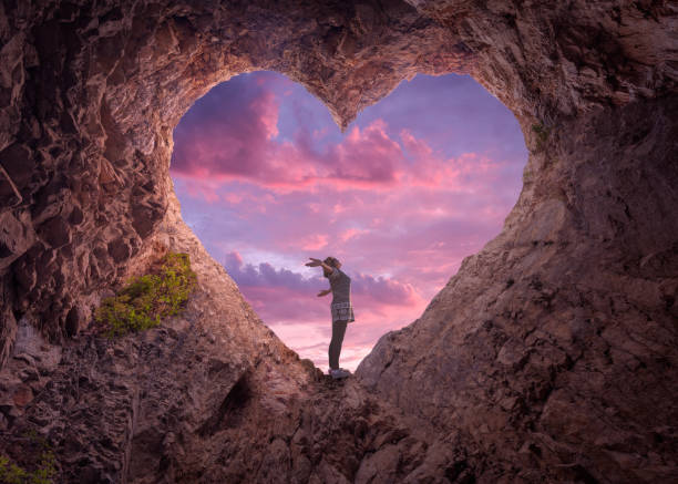 young woman in heart shape cave towards the beautiful sky - love stock photos and pictures