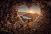 istock Young woman in heart shape cave towards the idyllic sunrise 873620504