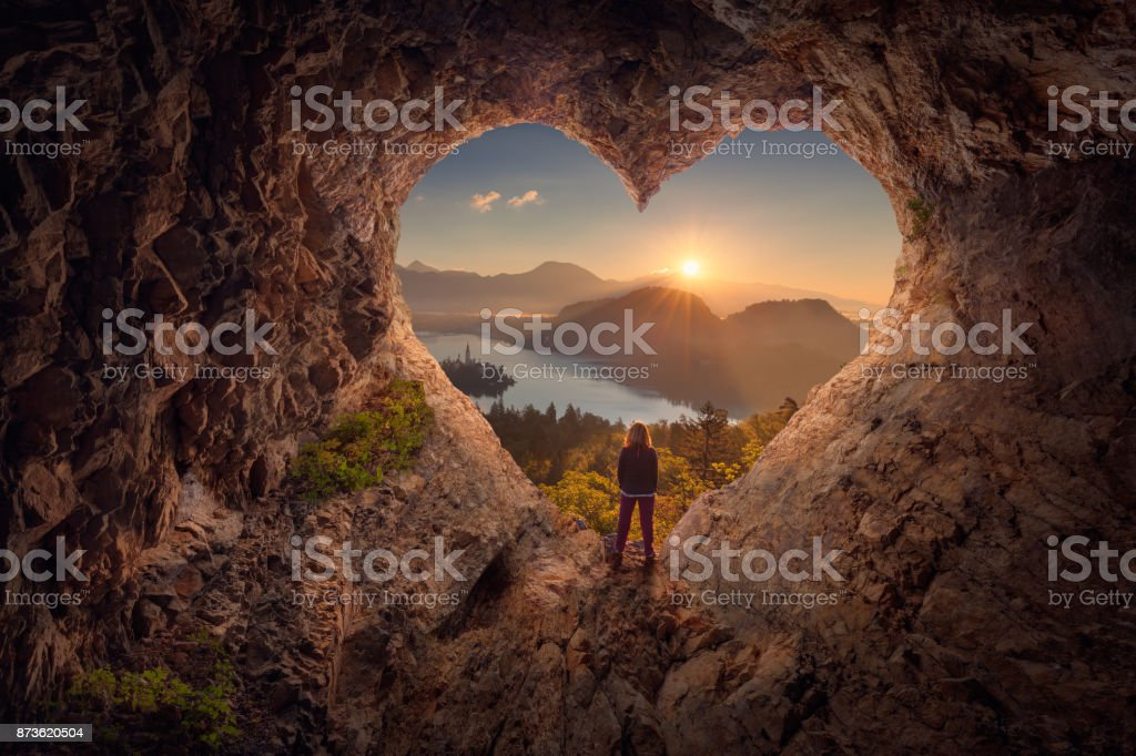 Young woman in heart shape cave towards the idyllic sunrise - fotografia de stock