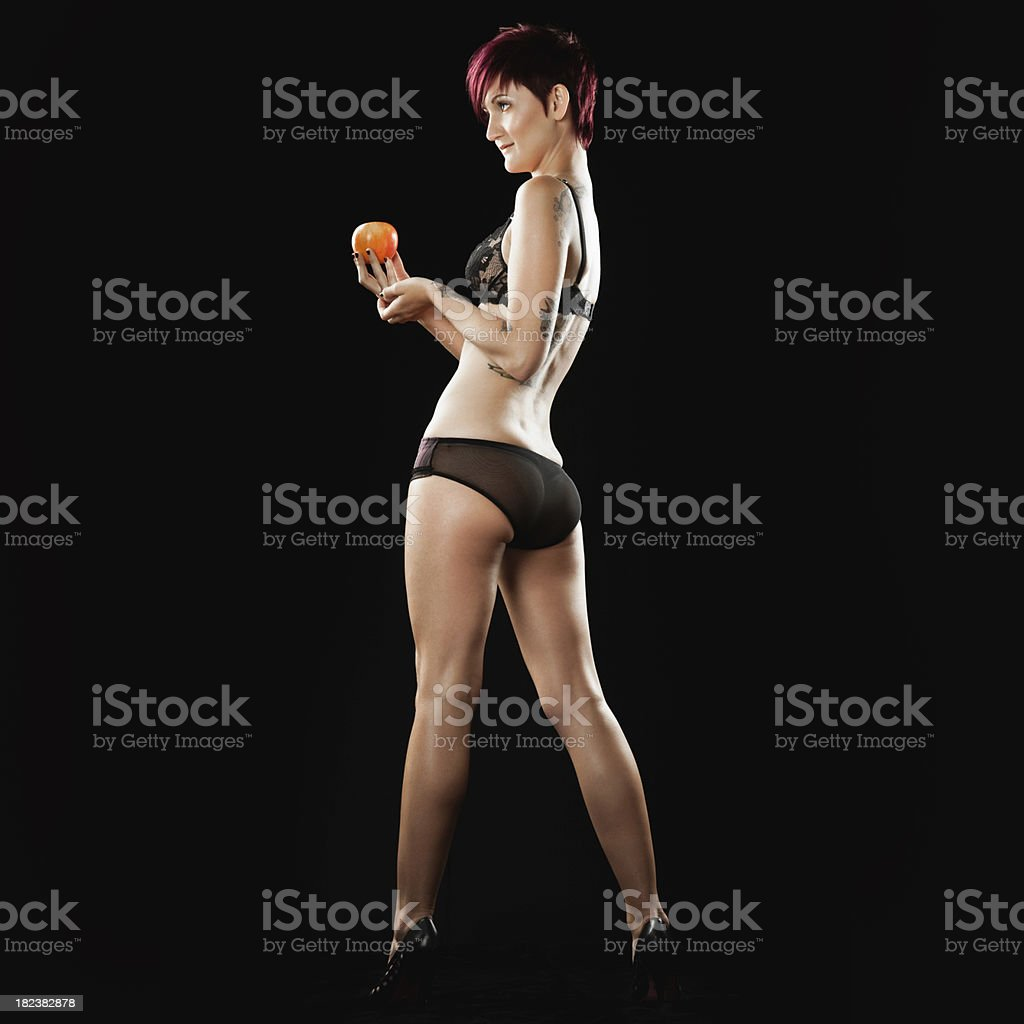 Young woman in her underwear holds an apple, full body royalty-free stock photo