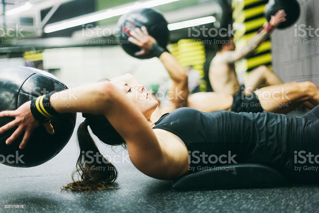 Young woman in high intensity fitness session. One young woman working hard in the gym. More files of this series on port. She is doing pushups from a a fit bench.  25-29 Years Stock Photo