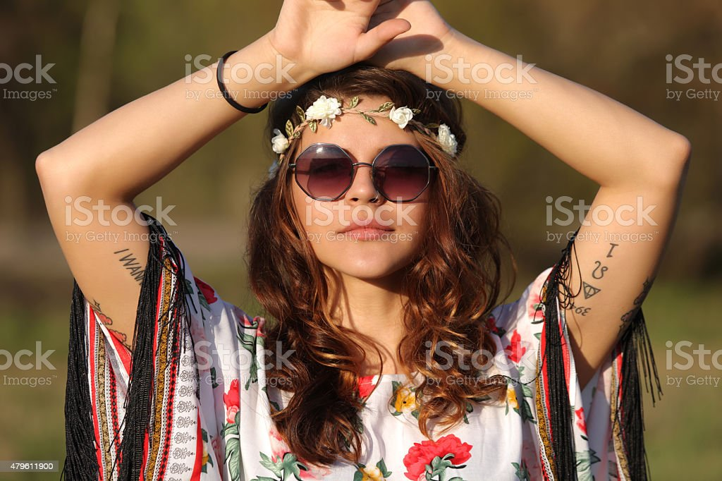 Young woman in hippie style Young woman in hippie style looking at the camera and holding hands on heads 2015 Stock Photo